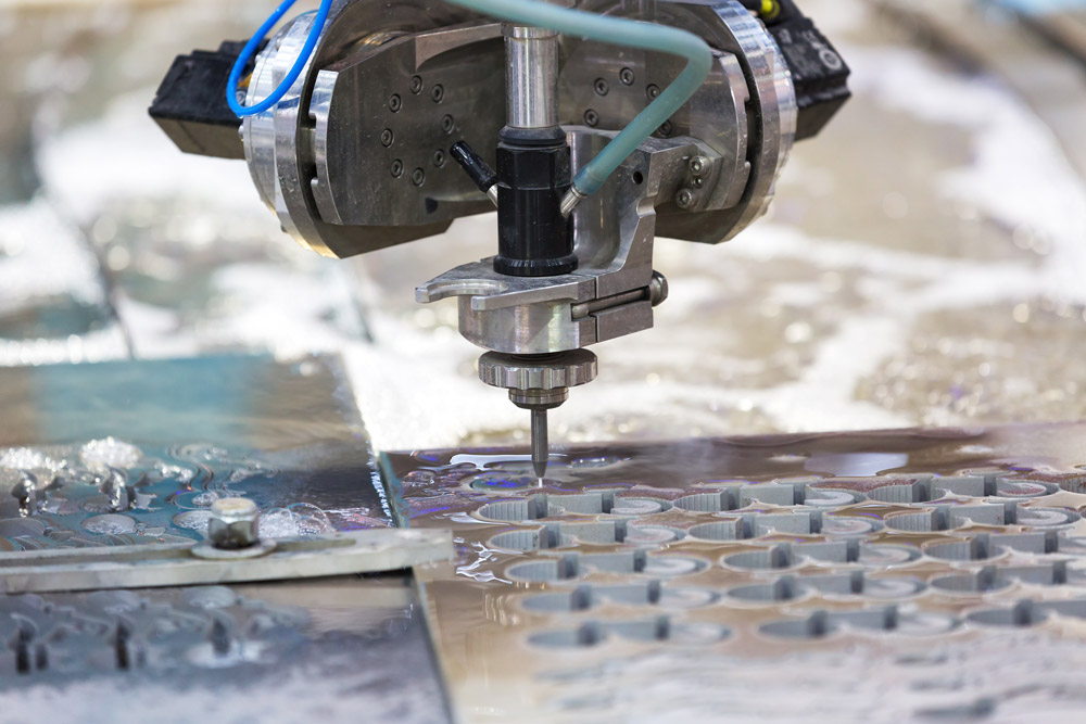 a waterjet cuts intricate shapes into steel material